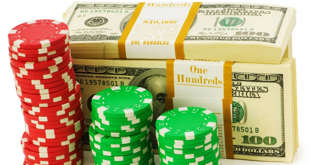 Casino bonus chips staked in front of a stack of dollar bills.
