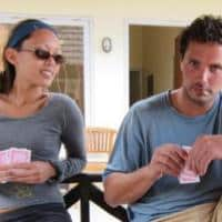 A man and a woman playing poker and Blackjack. The woman glances over her shoulders and secretly peaks the man's cards. This is called angle shooting.