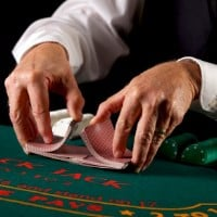A dealer in a casino is shuffling cards on the picture. Shuffle tracking is one of the methods used to make money gambling by eliminating the house edge.