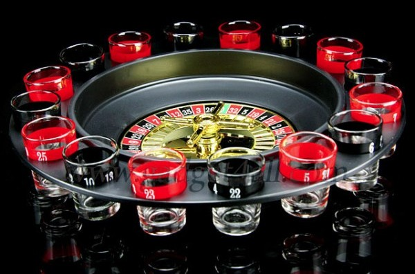 The picture depicts a Roulette wheel. However, this is not just an ordinary Roulette wheel. Apart from being a functional gambling device, this is also a prop for a drinking game. There are black and red numbered shoot glasses around the Roulette wheel. After spinning the Roulette wheel participants must drink from the corresponding shot glass.