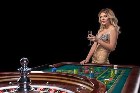 The picture is a screenshot of Roulette table in a casino with a woman holding a champagne glass. The screenshot was taken while the Roulette wheel was spinning, after the bets were placed. You can find the various roulette games on this website under the picture. By clicking on the picture you will be taken to the roulette page of the website.