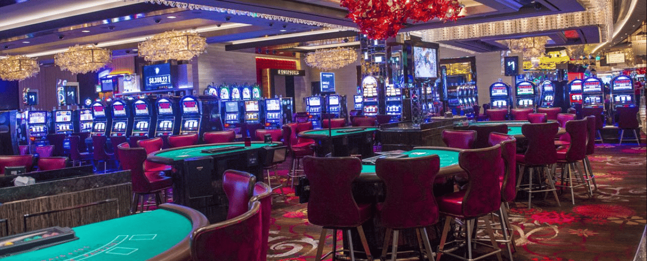 The image consist of the interior of a casino with gaming machines, a roulette wheel, and card tables visible. On this page, under the picture, you can find the 4 categories of free online casino games. These are: slots, blackjack, roulette, video poker, about 200 games all together. You can try out these free to play mobile compatible digital casino games by clicking on the links below.