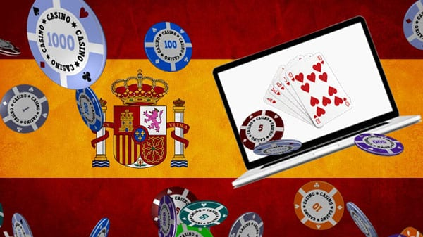The picture consist of a Spanis flag in the background with various online gambling paraphernalia in the foreground (laptop displaying an online casino website, computer generated casino chips and video poker).