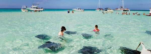 People with inflatable dolphins bathing in the sea on a beach in the Cayman Islands. Cayman Islands is notable for not even letting cruise ships to have their on-board casinos open while in port or in the territorial water. Read all about it below the picture.