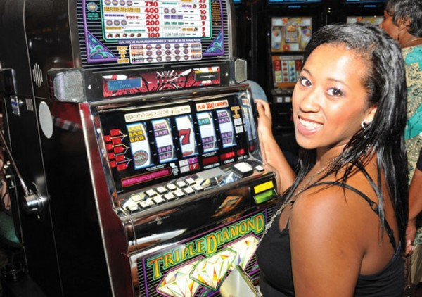This is a picture of a creole woman playing the Triple Diamond slot machin in the Ma Pau Entertainment Centre, a casino located in Dominica.