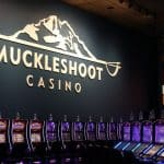 This is a picture of a row of slot machines inside Muckleshoot Casino Resort. This is the biggest Indian casino in Washington. Next to the picture you can read about the gambling establishments, the legal status of online casinos, crypto casinos and tribal casinos in WA, taxation of winnings and legal gambling age in the state.