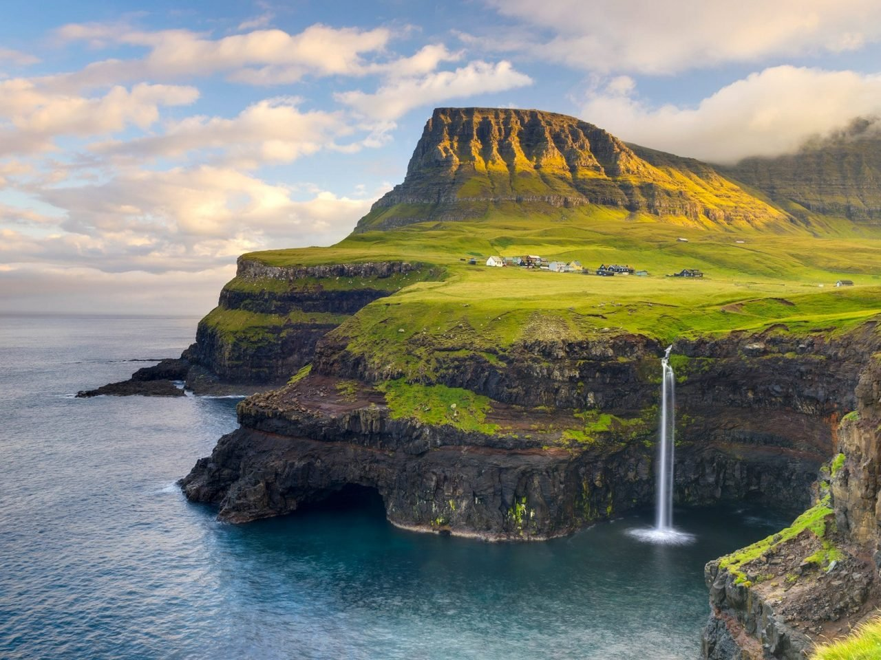 This is an aerial shot of the Faroe (Faeroe) Islands' beaches and small town and a waterfall. Under the picture, on this page you can read about gambling and online gambling in the Faroe Islands.