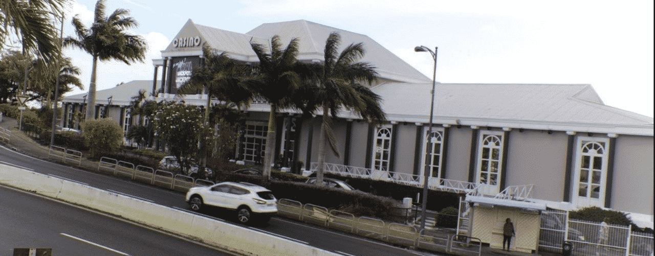 This is a picture of the front facade and main entrance of Casino des Trois Ilets, the biggest gambling establishments in the Overseas department of Martinique. On this page, you can read about the legislation, rules, licensing, taxation of of the various forms of games of chance and online gambling in the country, including: poker, bingo, lottery, sports betting, cryptocurrency wagering, and a slit of online gambling sites which accept players from Martinique.