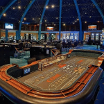 This is a picture of Hilton Aruba Caribbean Resort & Casino's gaming floor with the roulette table visible. You can read the details of the casino: number of games, opening hours, dress code, types of games, entrance fee, age requirement to the right of the picture.