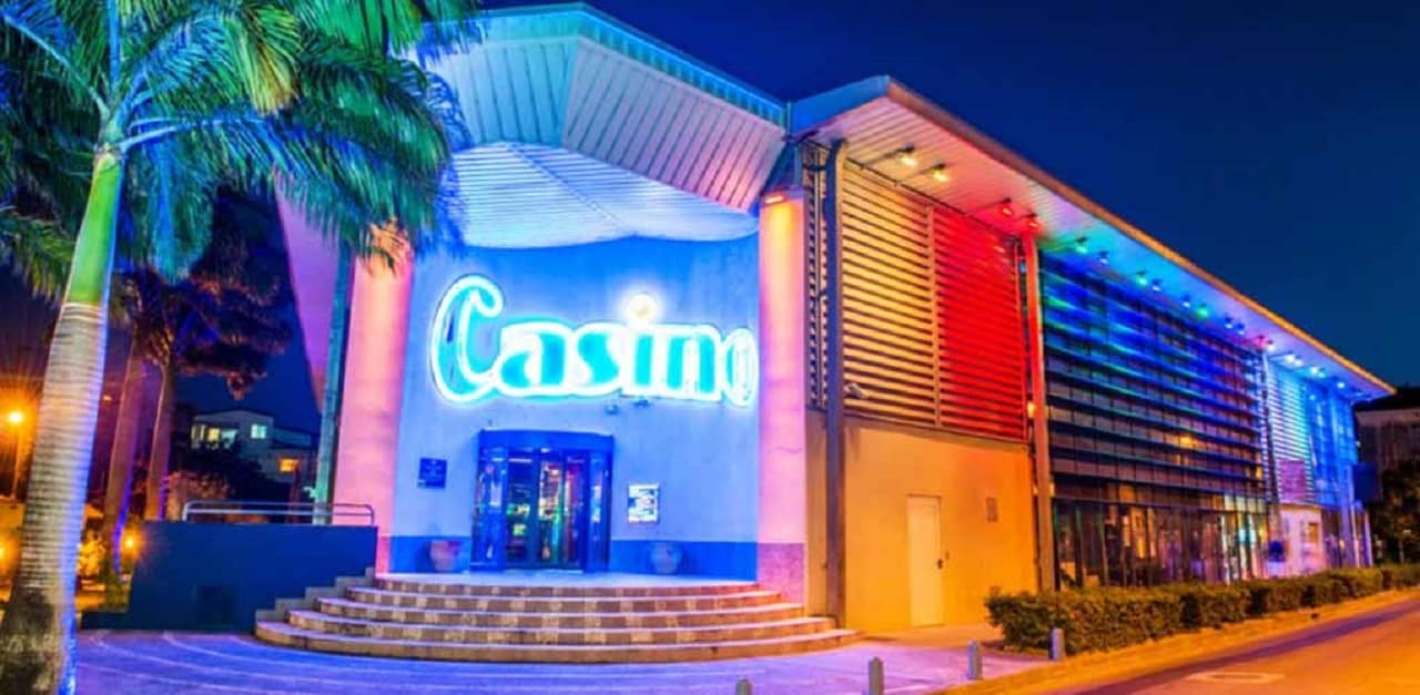 This is a picture of the building and front entrance of Casino des Trois-Ilets, the biggest casino of Martinique. On this page you can read about the taxation, legislation, licensing of casino gambling on the island, and you can find a list of licensed casino gambling establishments, slot halls and online casinos, which accept players from the Territorial Collectivity of Martinique - Collectivité territoriale de Martinique, a. k. a. Matnik.