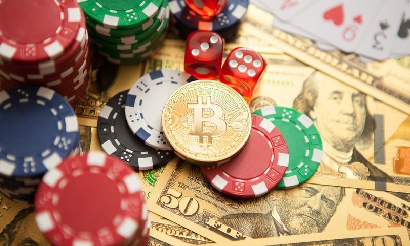 This is a picture of a bunhc of casinos chips, one plastic bitcoin chip, and a bunch of dollar bills on a table. On this page you can read a summary of my 12 years of experience working in the gambling industry as an online marketing professional and affiliate blogger.